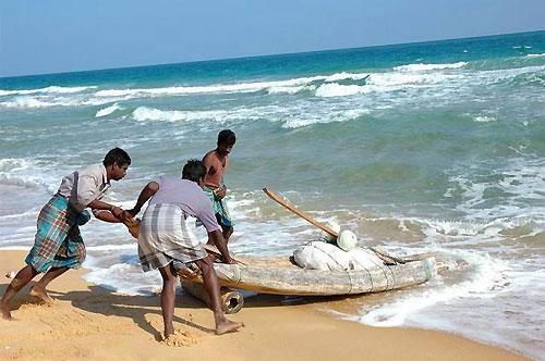 ボートを海に押し出す漁師