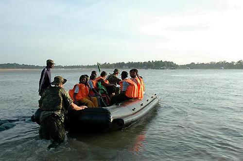 橋が流された村では、カナダ軍がボート輸送する