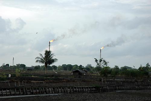 オレンジ色の炎を出しているのは「アルン社」天然ガス田の煙突。敷地は広大で、端から端まで車で数十分もかかる。300mm望遠レンズ使用(撮影:筆者)