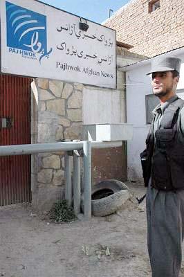 玄関前を警備する警察官。右肩にショットガンを下げている。