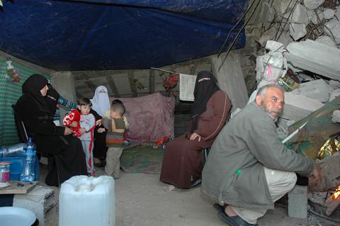 瓦礫の隙間で一家20人が暮らす。ハドゥルさん(右端)は雨水でコーヒーをたてていた(筆者撮影)