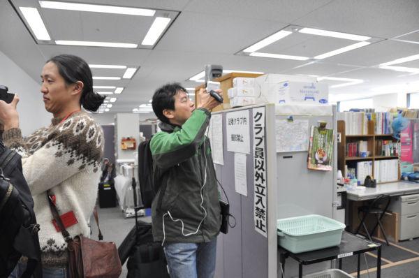 大坂城の千畳広間を思わせる広大な記者室をビデオ撮影するフリーランスの寺澤有氏(右側の緑色ジャンパー)。ご法度破りである。=11日、総務省記者クラブ。写真:筆者撮影=