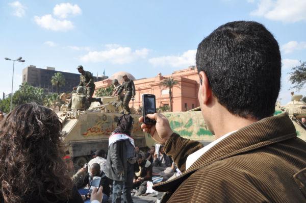 戦車前に座り込んだ「ムバラク打倒派」の人々を携帯電話の内蔵カメラで撮影する市民。(タハリール広場。写真:筆者撮影)。