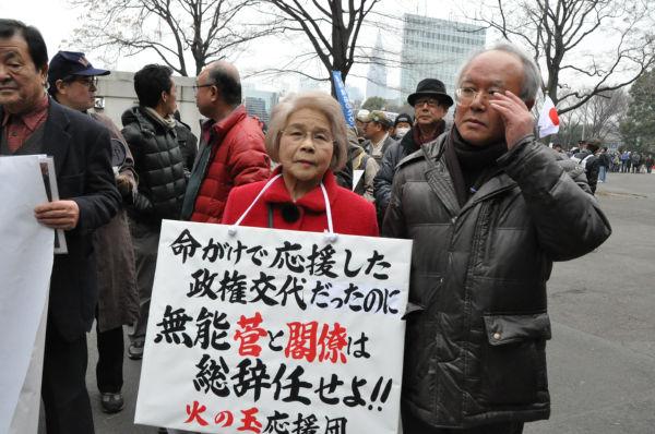 国民を裏切った菅政権への怒りは強い。右隣の男性は検察の裏金を告発したため逮捕・起訴された三井環元検事。(20日、明治公園。写真:筆者撮影)