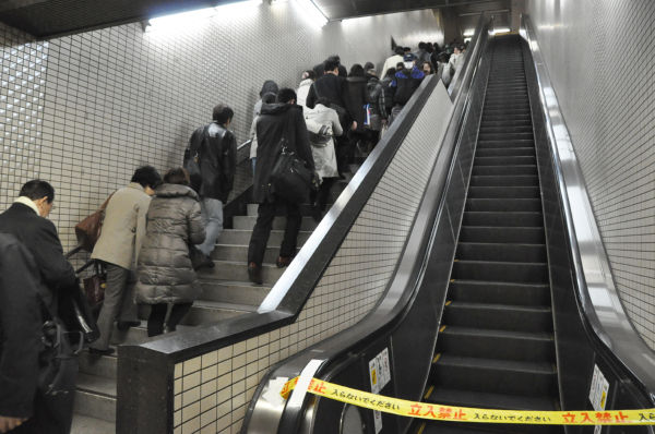 節電のためエスカレーターが停まった地下鉄駅構内。利用者は息を切らしながら階段をのぼる(18日、東京・中央区。写真:筆者撮影)。