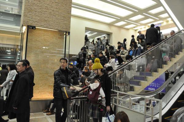 運転復旧のメドが立たないことから、駅構内の階段に座り込む人たち。(11日、JR新宿駅構内。写真:筆者撮影)