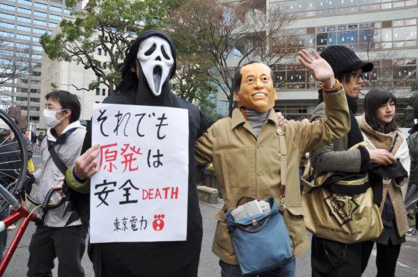 大地震発生翌日、菅首相は福島原発を視察したが東電から「大丈夫です」と騙された。「死神・東電」と「無能・菅」を皮肉ったコスチューム。(27日、日比谷公園。写真:筆者撮影)