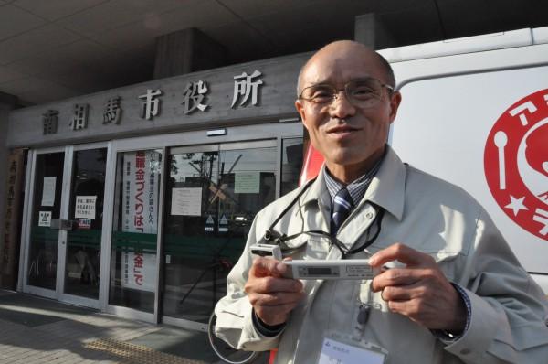 桜井勝延市長は被曝カウンターを手放さない。手にしているのは原子力保安院から、右胸ポケットは日本原子力機構から提供された。(3日、南相馬市役所前。写真:筆者撮影)