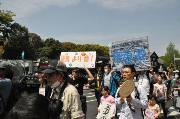 自家製のプラカードを手にデモに参加する家族連れ。(16日、原宿駅前。写真:筆者撮影)
