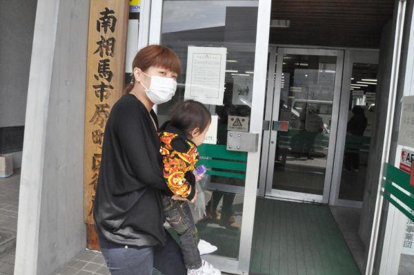 脱出したくても脱出できない母親と幼児。マスコミはいち早く逃げ、あげくに「ただちに人体に影響はない」と伝える。住民をバカにした行状だ。(3日、南相馬市役所。写真:筆者撮影)