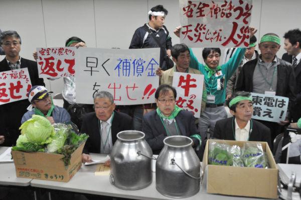 損害賠償請求書を手渡しに東電を訪れた福島県の農民。大きなボトルには牛乳が入っている(26日、東京電力別館。写真:筆者撮影)