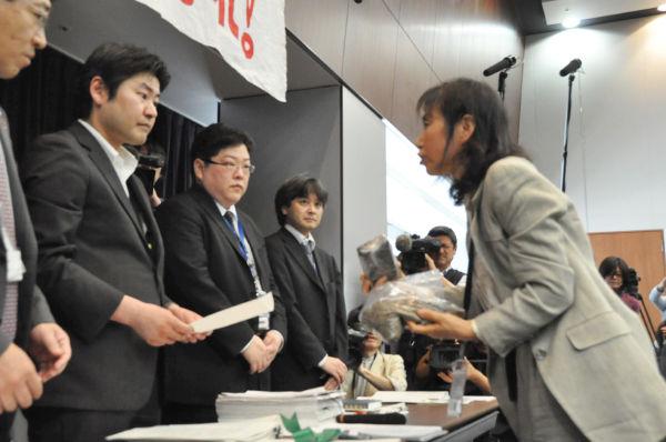 厚労省の担当者に福島市内の小学校の土を渡す佐藤幸子さん。(2日、参院会館。写真:筆者撮影)