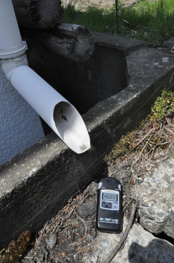 雨樋の下にカウンターを置くとケタ違いに高い線量を示した。(25日、飯舘村長泥。写真:筆者撮影)