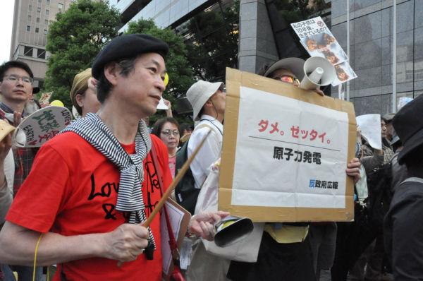 真っ赤なシャツにパーカッション。お祭り気分に湧く抗議集会だ。(14日、東電本店前。 写真:筆者撮影)