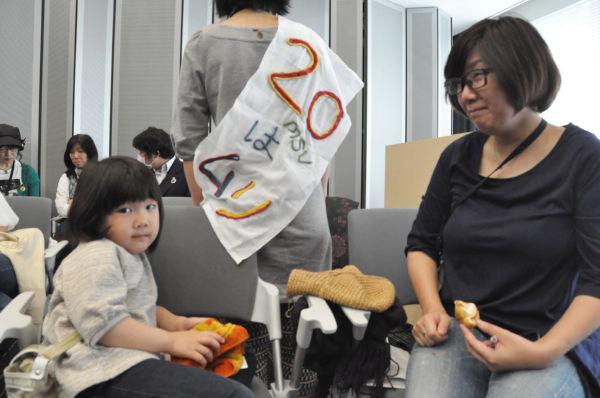 郡山市から東京に避難してきた母と子。タスキの女性は福島出身。(2日午後、参院会館。写真:筆者撮影)