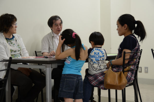 医師らの問診を受ける母と子供たち。長いケースでは40分にも及んだ。(23日、港区芝公園。写真:筆者撮影)