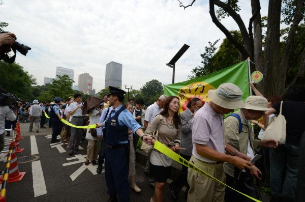 警官隊が張る非常線の中を会場に進む株主たち。(写真:筆者撮影)