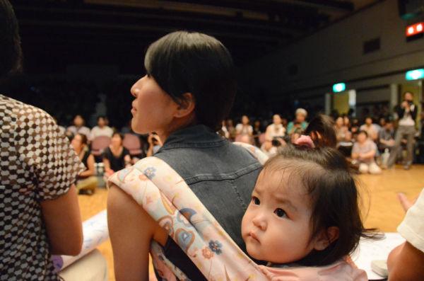 幼な子をおぶって参加する母親の姿も目立った。(12日、全電通労働会館。写真:筆者撮影)