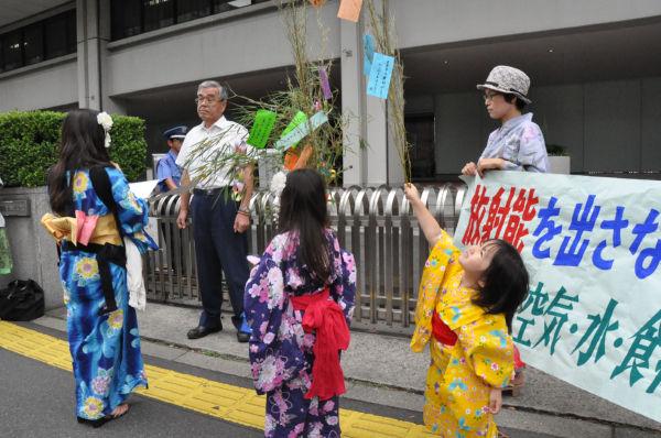 母親代表の横関さんは東電警備長に要請文を子供たちは短冊を手渡した。警備長の上から目線が東電の体質を象徴しているようだ。(7日夕、東京電力電正門前。写真:筆者撮影)