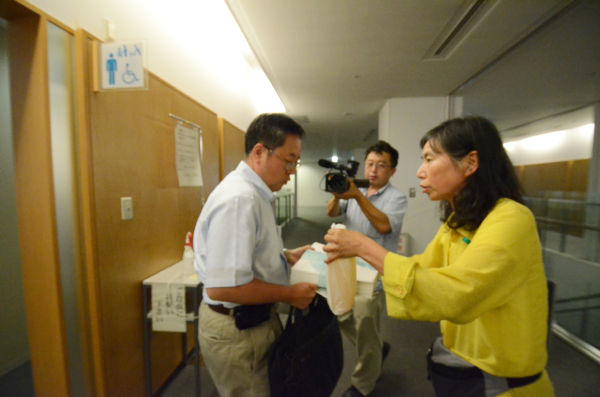 現地対策本部の佐藤室長が署名と尿を持たずに帰ろうとしたため、母親は追いすがり力づくで持たそうとした。(筆者撮影)