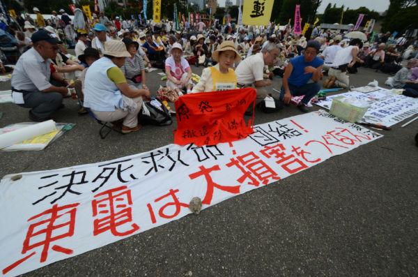 手書きの横断幕を持ち込んだ酪農家の吉沢正巳さん=右・青シャツ。(2日、明治公園。写真:筆者撮影)