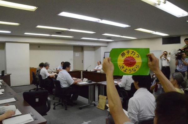 ポスターを掲げて原子力委員会の無責任さに抗議する男性。(内閣府で、筆者撮影)