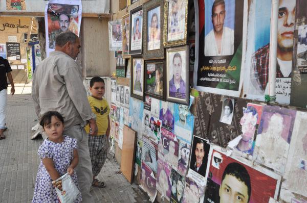政治犯収容所で虐殺された親族の遺影を探す男性。誰が民衆の敵なのか、はっきりしていた。(8月26日、ベンガジ市内。写真:筆者撮影)