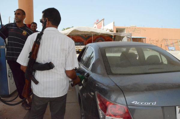 ガソリン不足に見舞われるリビア。GSの従業員は襲われないようにカラシニコフ銃を肩に給油する。(トリポリ―ミスラータ街道のGSで。筆者撮影)