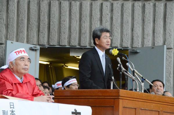 挨拶する中川俊男・日本医師会副会長。「TPPは日本の医療に深刻な影響を及ぼす」。左(赤ジャンパー)はJA全中の萬歳章会長。=26日、日比谷野音。写真:筆者撮影=