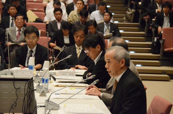 原子力損害賠償審査会で誇らしげに説明する東電・廣瀬常務(手前)。被害者への補償が、さも順調に進んでいるかのようだった。=20日、文科省。写真:筆者撮影=