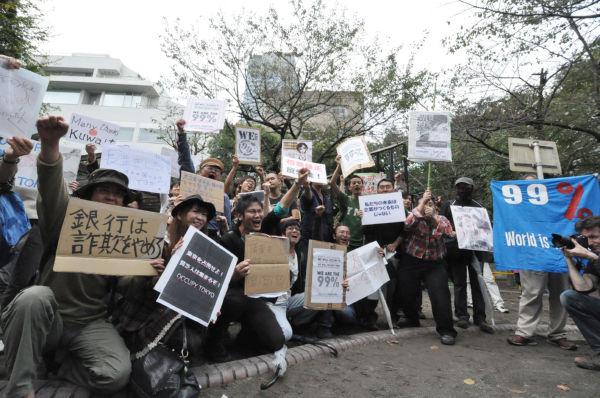 格差撲滅へのメッセージを綴ったプラカードを手に気勢をあげる参加者たち。(15日、六本木・三河台公園。写真:筆者撮影)