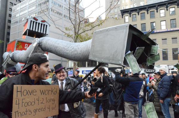 怪物のニューヨーク・スロット・エクスチェンジに金を吸い取られる庶民。プラカードに書かれた数字の4はfor、2はtoo 。=写真:筆者撮影=