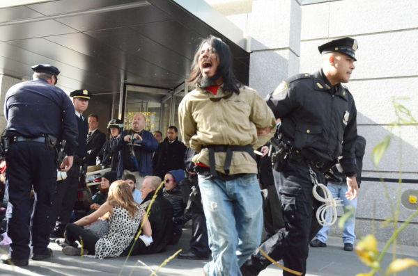 「(警察は)恥を知れ」。青年が逮捕、連行されるとデモ参加者から非難の声があがった。=3日(現地時間)、ゴールドマン・サックスが入居するビルの玄関前。写真:筆者撮影=
