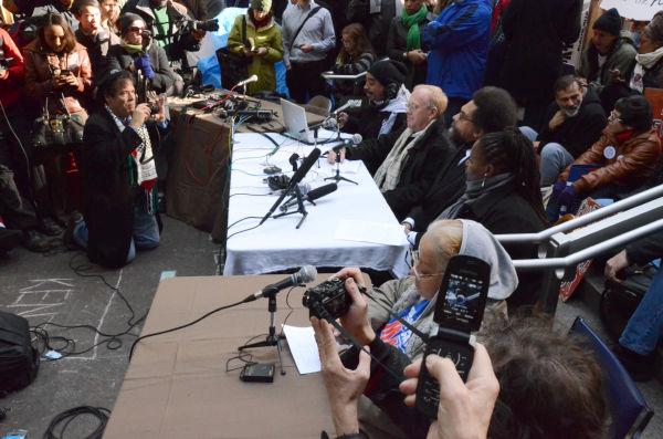 市民集会で「Occupy(占拠)行動」を鼓舞するクリス・ヘッジズ記者(テーブル席の奥から2番目)。=同日、ズコッティ・パーク。写真:筆者撮影=