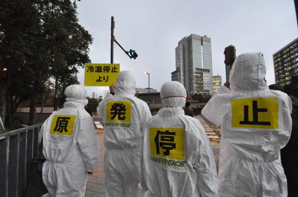 「冷温停止より原発停止」。放射能防護服を着て抗議するグリーンピースのメンバー=16日夕、首相官邸前。写真:筆者撮影=