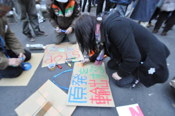 女性はデモ集合場所にマーカーとダンボールを持ち込み「原発を輸出するな」と書いた。=日比谷公園。写真:筆者撮影=