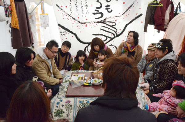 椎名さん(正面左角、はんてん姿の女性)の話に聞き入る来訪者たち。=写真:28日午後、写真:中野博子撮影=