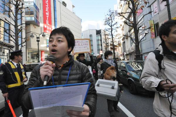 大阪から参加した学生(手前)。「最初は震災復興、原発事故で政治に関心があったが、最近は雇用問題と就職で政治家にしっかりしてもらいたいと思うようになった」。=写真:中野博子撮影=