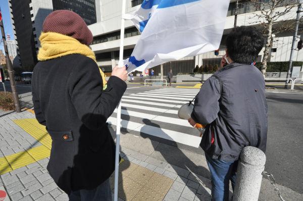 寒風のなか訴えを続ける2人。東電正門前の警察官とガードマンが遠巻きに監視する。=写真:筆者撮影=