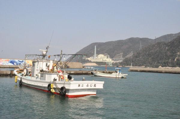トラブルメーカーの『もんじゅ』と小さな漁船がミスマッチだ。=敦賀市白木の漁港より。写真:筆者撮影=