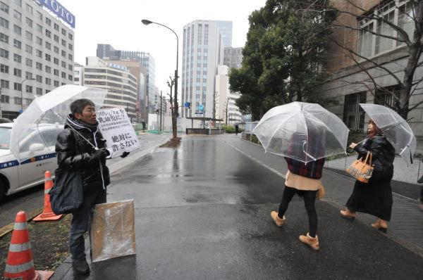 冷たい雨に打たれながら「子どもを被曝させるな」と訴えた。=文科省前。写真:筆者撮影=