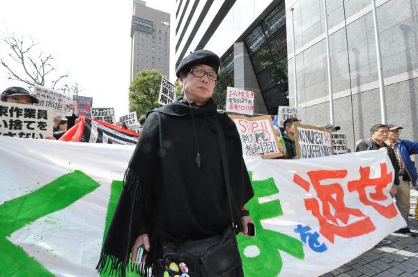 黒装束の男性は「人の心を失くした東電に対する喪でもある」。=11日午前、東電前。写真:筆者撮影=