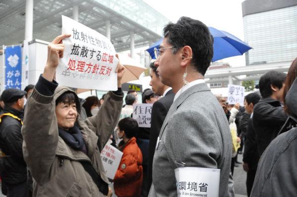 環境省職員(腕章の男性)に面と向かって『受け入れ反対』のプラカードを掲げる住民。=18日、JR川崎駅頭。写真:筆者撮影=
