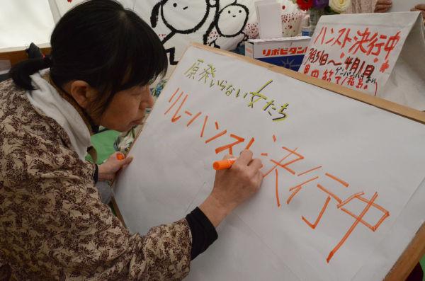 「ハンスト決行」の看板を作製しているのは、『原発いらない福島の女たち』共同代表の椎名千恵子さん。=撮影:筆者=