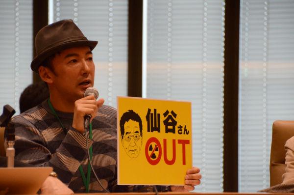 山本太郎さんは友人が製作したパネルを持ち、野田政権に再稼働の号令をかける仙谷氏を皮肉った。=19日、衆院会館。写真:筆者撮影=