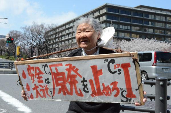 益永スミコさん。「死んどる暇はない」と元気だ。後方は外務省。=経産省前交差点。撮影:諏訪 京=