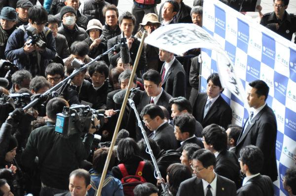 「瓦礫受け入れキャンペーン」のため訪れた京都で、ぶら下がり記者会見に応じる細野大臣。諏訪(手前・赤いリュック)が追及したが、噛み合わない答えしか返ってこなかった。=31日、京都駅前。撮影:田中龍作=