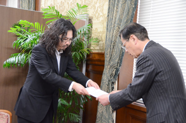2万筆余りの署名を添えた要請書を稲見議員に手渡す平野さん。=写真:筆者撮影=