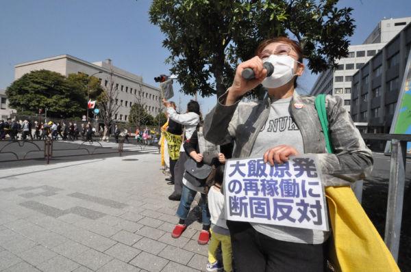 「再稼働反対」を訴える太さんらの傍を「消費税反対」のデモ隊が通り過ぎて行った。=写真:筆者撮影=