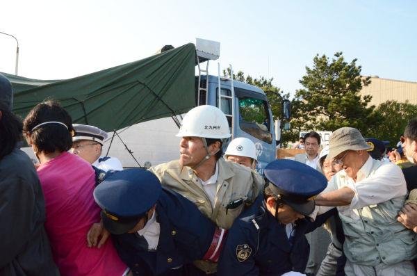 住民たちはトラックが入るのを止めようとして、警察隊と激しい揉みあいになった。=22日午後5時30分、北九州市日明積出基地。写真:筆者撮影=